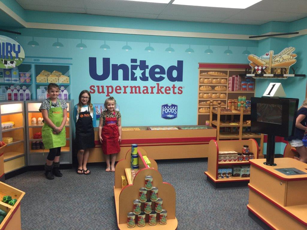 Picture of Three little shopkeepers gave store tours and checked out happy guests shopping on opening day.